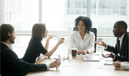 4 People sitting at a table in a board room.